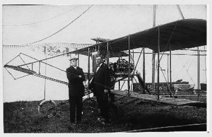 """Pilot Lee Hammond (left) pictured with Captain Thomas Baldwin next to his """"Red Devil"""" airplane ON September 11, 1911. Hammond is credited with the first airplane flights in the City of Ottawa, a five minute circuit over the Central Canada exhibition grounds, out to Dow's Lake, and then landing at Slattery's Field, which today is the site of Hydro Sub-Station 5 at 39 Riverdale. Photo By Rick Wallace: Online History Of Ottawa East Photos"""