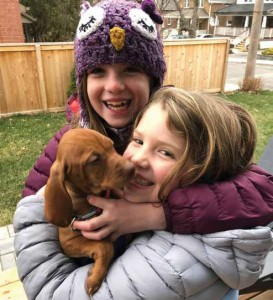 Claire and Emily hug new family member, Poppy, as they prepare for her first walk in the neighbourhood. Photo Supplied